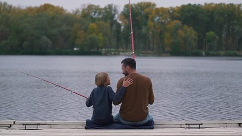 Dad encourages his son on fishing.