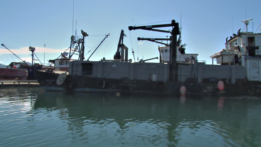 HOMER, AK - CIRCA 2012: Utility boats, cargo boats, landing craft, fishing boats, tug boats, crabbing boats. We pass them all at their moorings, side view from our boat.