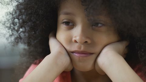 Lonesome Afro-American female kid looking up and thinking about friends, closeup