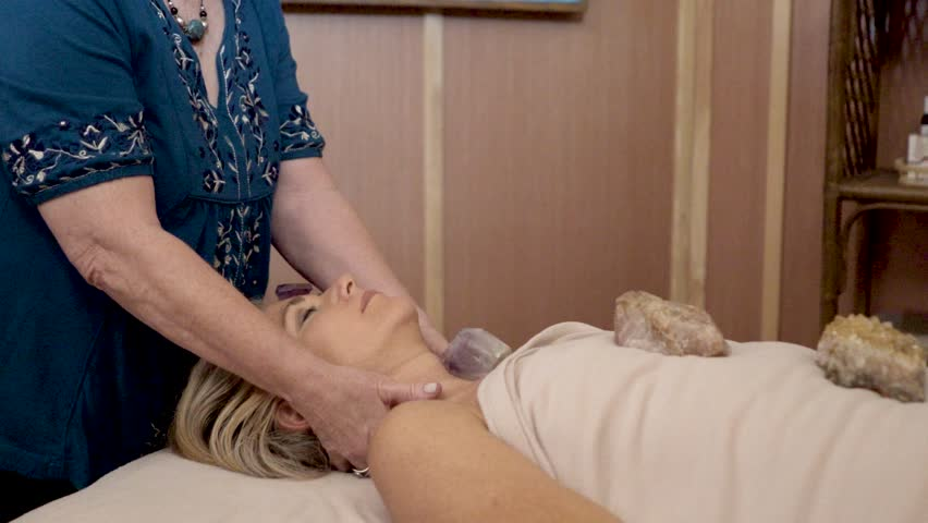 Camera pushing in on a therapist using crystals and her hands to energize healing powers for a mature woman