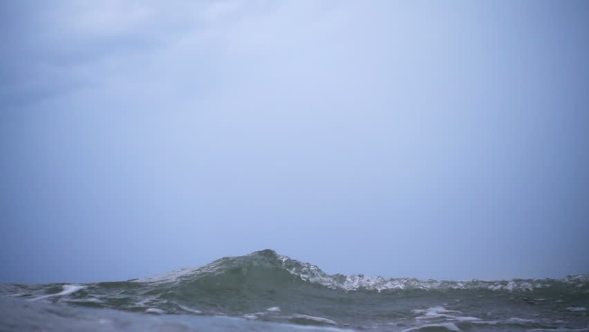 Waves on the ocean. The camera goes under water. Video recorded in slow motion.