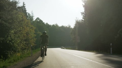 Person riding a bike fast down the road in the morning. Concept of persistence and the will to improve oneself. Never give up.