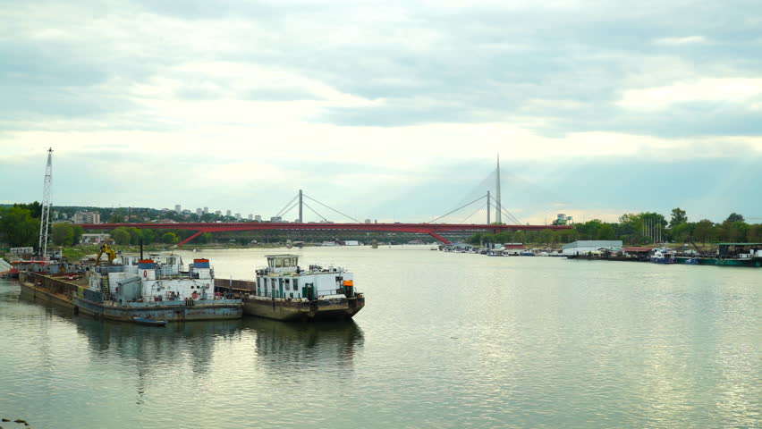 Tugboat and cargo ship docked on the riverside, many boats, vessels and ships in dock on the other coast of the river, suspension bridge and city in the background, landscape. | Shutterstock HD Video #31587685