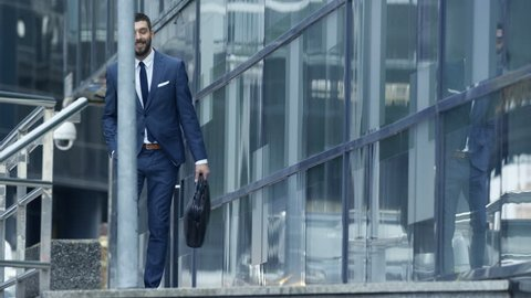 Happy Smiling Business Man with a Bag Goes Down the Stairs and Checks His Smartphone, He's in the Business District. Shot on RED EPIC-W 8K Helium Cinema Camera.