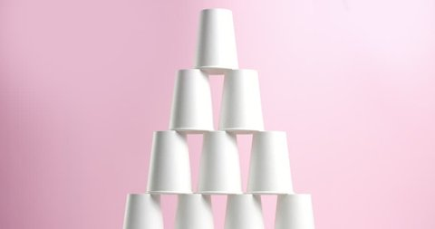 Tower made of white paper cups on pink background