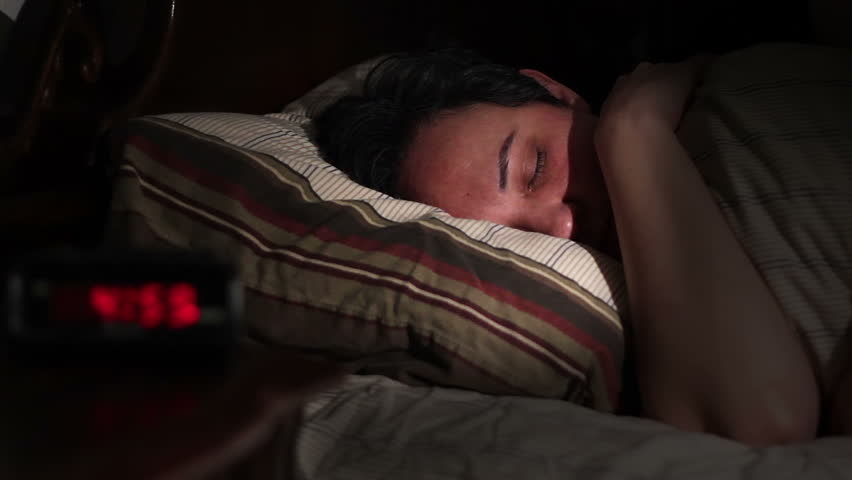 A woman wakes up & turns off her alarm clock.