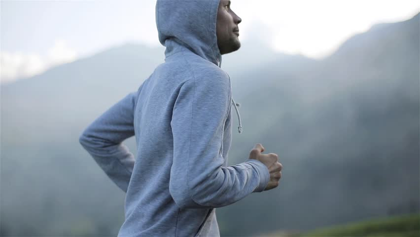 Man jogging on mountain road close up slow motion looking at camera front side view. Morning jogger moves hands running up valley hill in grey hood sportswear. Ambition goals training success concept