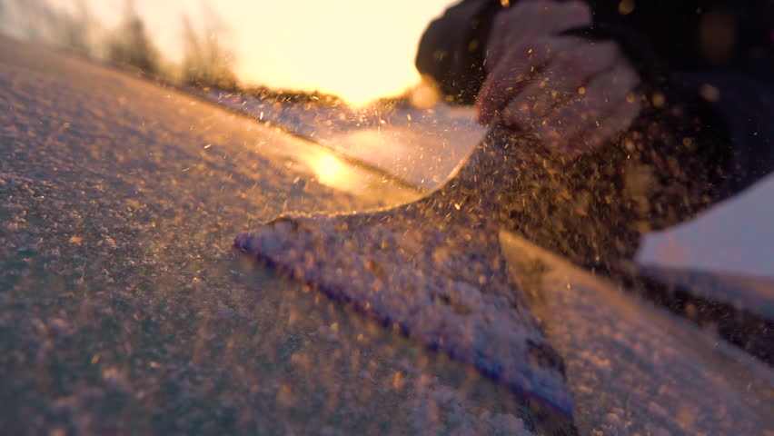 SLOW MOTION CLOSE UP DOF: Person cleaning morning frost off a car window at golden sunrise. Hand scraping hoarfrost off a frozen car windshield, snowflakes flowing over the sun. Scraper removing frost | Shutterstock HD Video #31622617