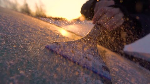 SLOW MOTION CLOSE UP DOF: Person cleaning morning frost off a car window at golden sunrise. Hand scraping hoarfrost off a frozen car windshield, snowflakes flowing over the sun. Scraper removing frost