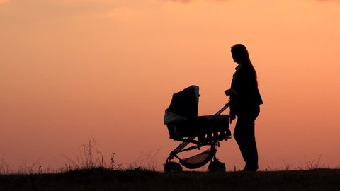 Woman silhouette walking with baby pram close sunset colored red sky