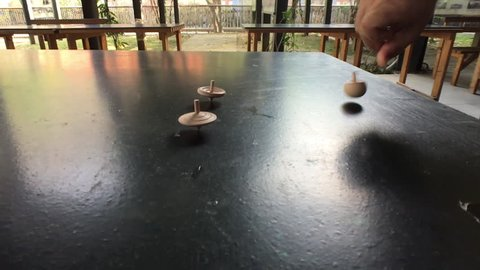Slow motion of three wooden tops spinning on a blacktop table outside.