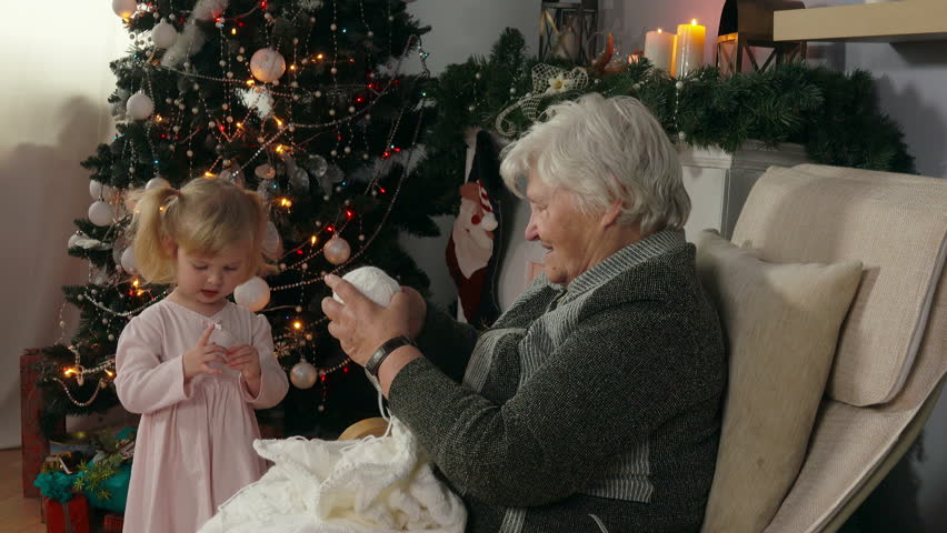 Grandmother knits, sitting in an armchair next to the fireplace. A little girl is playing with a ball of thread. Christmas party, elegant Christmas tree | Shutterstock HD Video #31655557