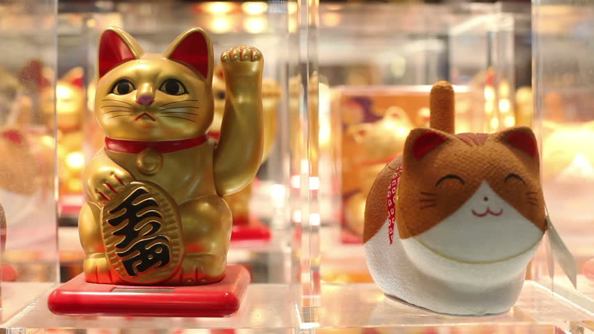 Maneki neko or beckoning cat in a window in Asia. Beckoning cats are placed in front of shops for good luck and attracting customers.
