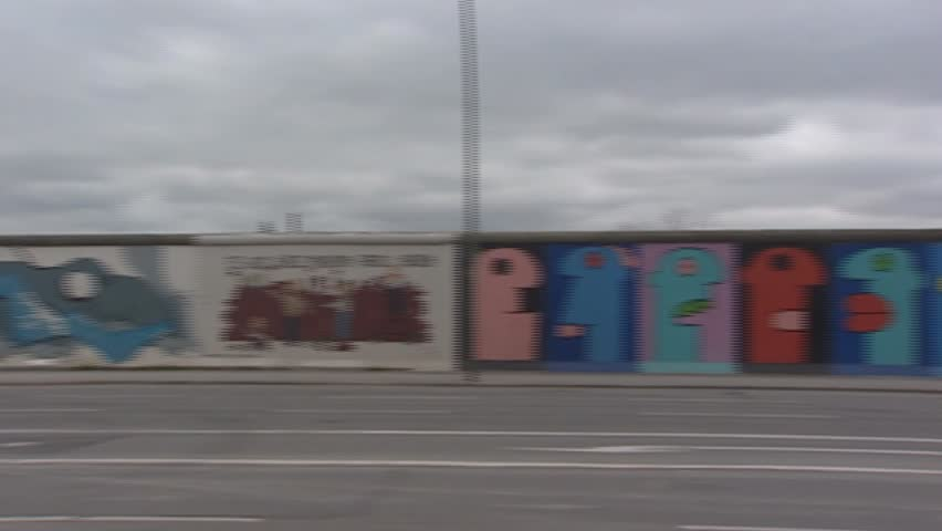 EAST SIDE GALLERY, BERLIN WALL, BERLIN - CIRCA 2002: panoramic shot.  Paintings by artists from all over the world cover this memorial for freedom and make it the largest open air gallery in the world