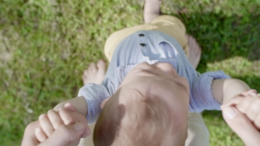 POV of woman holding hands of cute toddler walking on green grass in park on summer day