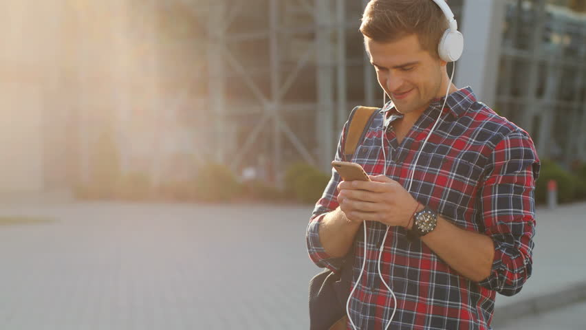Portrait of a happy young man with a backpack listening to music on his cellphone. Wearing headphones. Sun shining. Blurred background