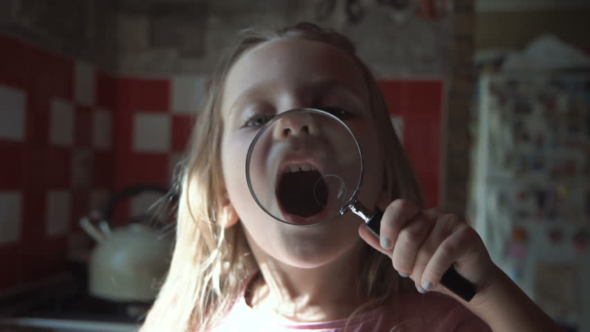 Smiling little girl playing and grimacing with magnifier on kitchen.