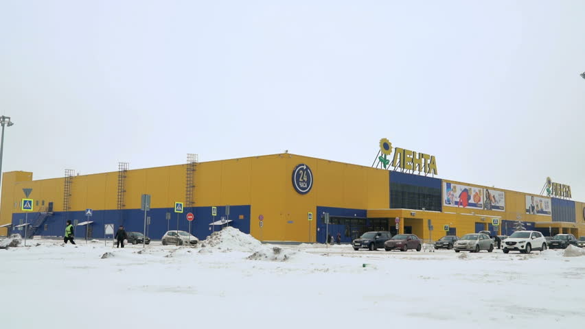 VELIKIY NOVGOROD, RUSSIA - JANUARY 07, 2017: Winter city landscape - big yellow hypermarket next to cars in the parking