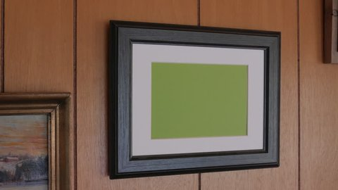 Photo frame hanging on wooden wall, horizontal. Tracking.