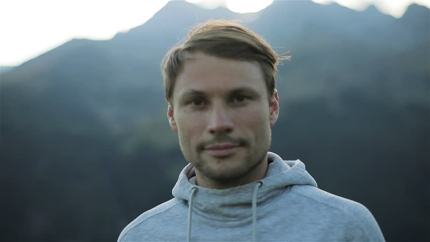 Portrait of man looking at camera face close up outdoors in mountains morning nature. Caucasian handsome confident calm 30s guy with loving kind brown eyes athlete sportsman traveler in grey sweater #31773667