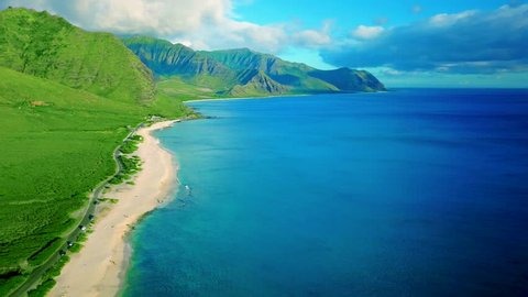 Aerial: Sexy Vibrant Lush Hidden Tropical Yokohama Beach, Oahu, Hawaii Island.  Flyover deep blue ocean and white sand beach and steep green mountain.  Romantic Green and blue colors with white sand.