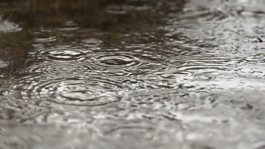 Rain drops dripping in a puddle - slow motion