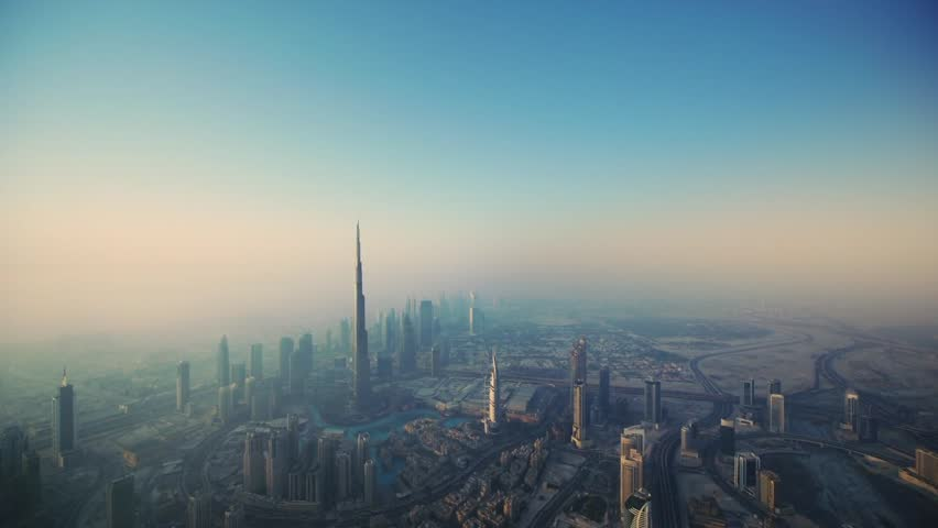 Magnificent aerial drone flight over futuristic tower huge skyscraper Dubai city in gradient morning pink fog sunrise