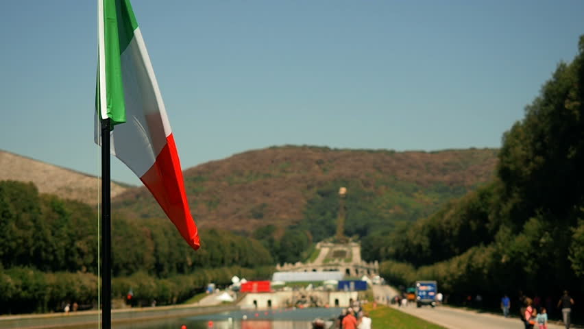 Flag of Italy waving in the wind. Italian countryside. Beautiful  flag blowing in wind: Italy. Tourism Italy Popular Tourist Attraction. Royal Residence in Italy