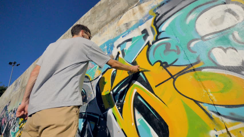 A low view on a man restoring a graffiti painting.