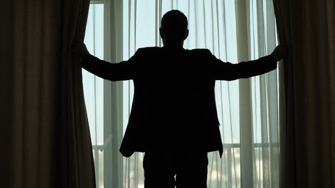 Guy standing against window, holding curtains by hands, black silhouetted view. Slowly move hands and close drapes, room become dark. Half length shot from back, slow motion