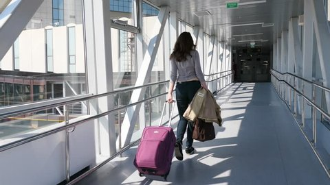 Passenger woman with trolley bag (large cabin luggage) walk through glass walled passage, come to airport terminal from airliner. Bright sun light and dark doorway ahead, follow camera move behind