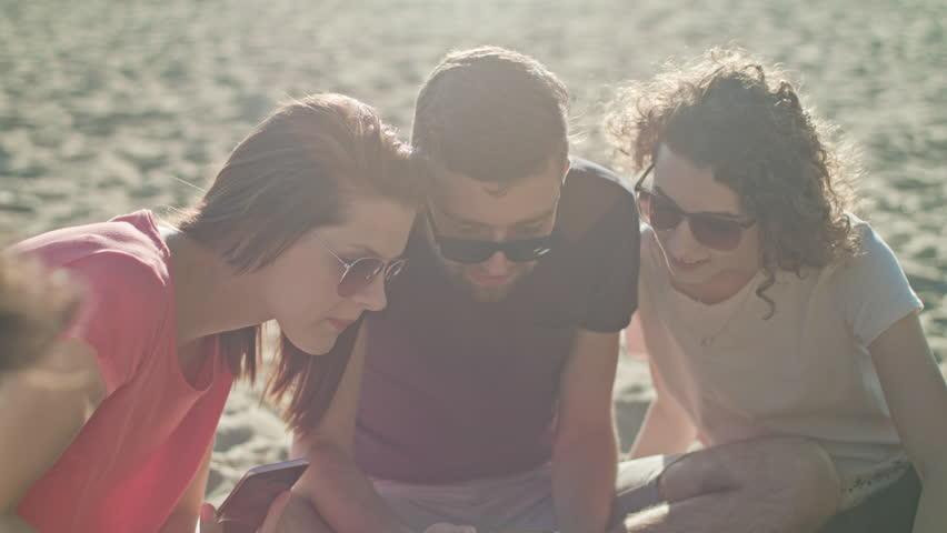Young people having fun on the beach using phones. Medium shot. Soft Focus.