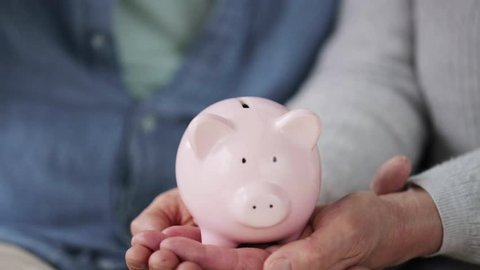 family, savings, old age and people concept - smiling senior couple putting money into piggy bank