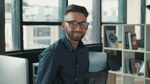 young man beard siting on the table in office, looking on the camera, wearing glasses, smiling. Feels happy. businessman, designer, programmer. Shot on RED EPIC camera. Slow Motion Shot.