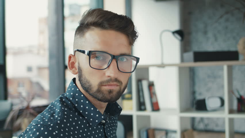 Stylish handsome serious man with glasses beard with blue eyes siting table in office, looking on the camera fixes the glasses businessman, designer, programmer. Slow Motion Shot. | Shutterstock HD Video #31843027