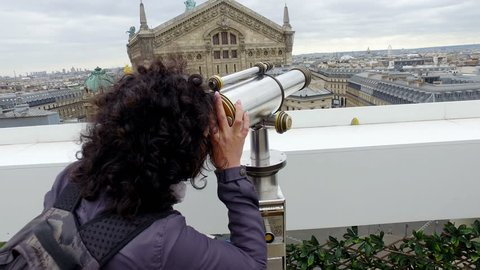 Tourists looking over Paris cityscape with Opera Garnier and Eiffel Tower on Lafayette Gallery terrace with coin operated binocular telescope