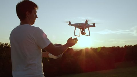 SLOW MOTION CLOSE UP LENS FLARE Young man hand launching quadro drone with modern white RC transmitter. Male filmer controlling drone over RC radio controller. Man flying and filming with drone camera