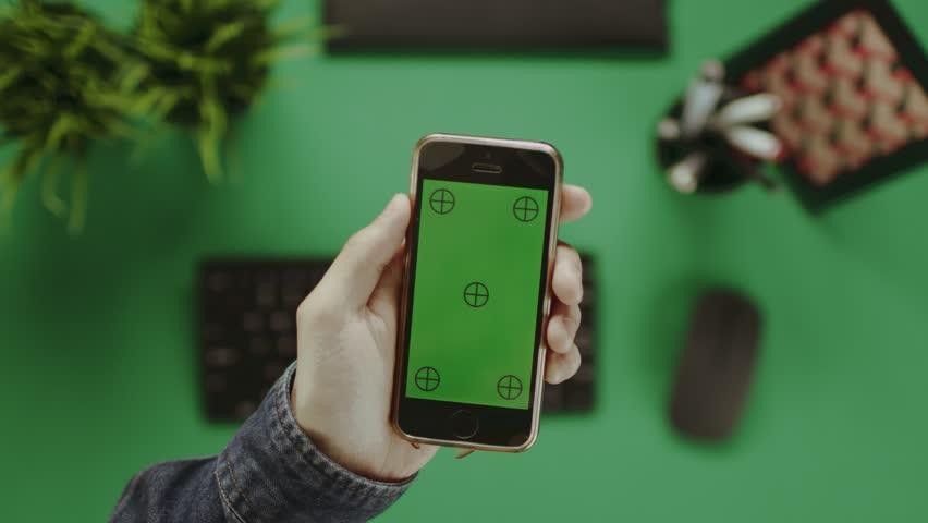 Overhead shot of man using smartphone with green screen | Shutterstock HD Video #31900777
