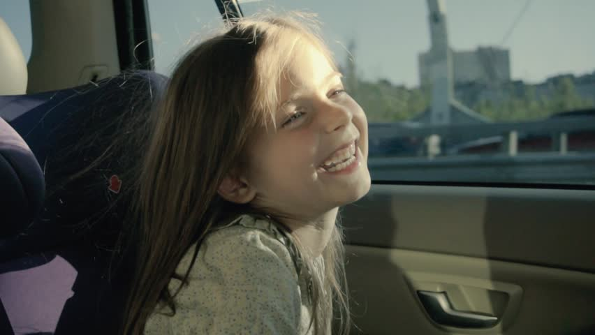 Happy funny girl in a car. Little girl in back seat looking through the window
