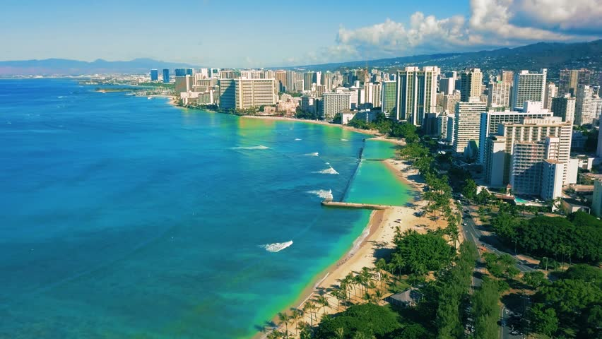 Colorful Aerial View of Tropical Waikiki Beaches in Honolulu, Oahu Hawaii Island. Vivid Blue-green ocean, white sand beach, relaxing vacation for tourist. Surfer's tropical paradise. 4K Drone.