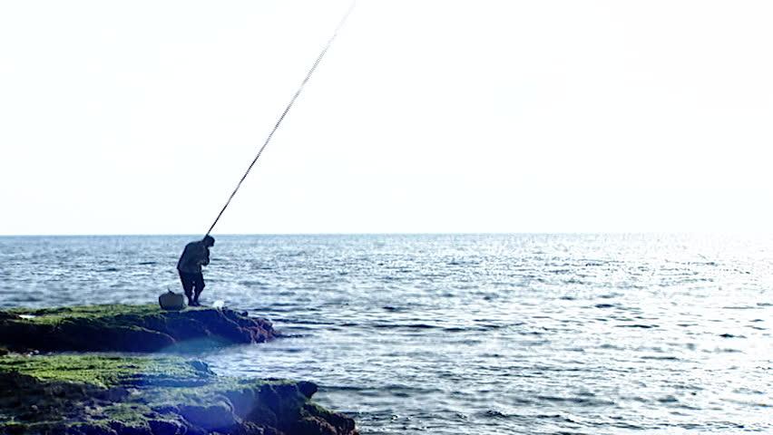 Fishing, Raouche, Beirut. WS of fisherman standing on rocks and fishing along the Lebanese coastline.