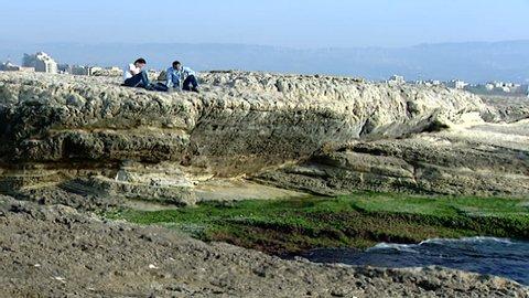 Beirut, Lebanon. Long-shot, pan-right of people sitting and walking on rocks along Beirut coastline.
