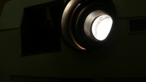 old Photo slide projector close up of the lens changing color and flashing light shot in 4 k