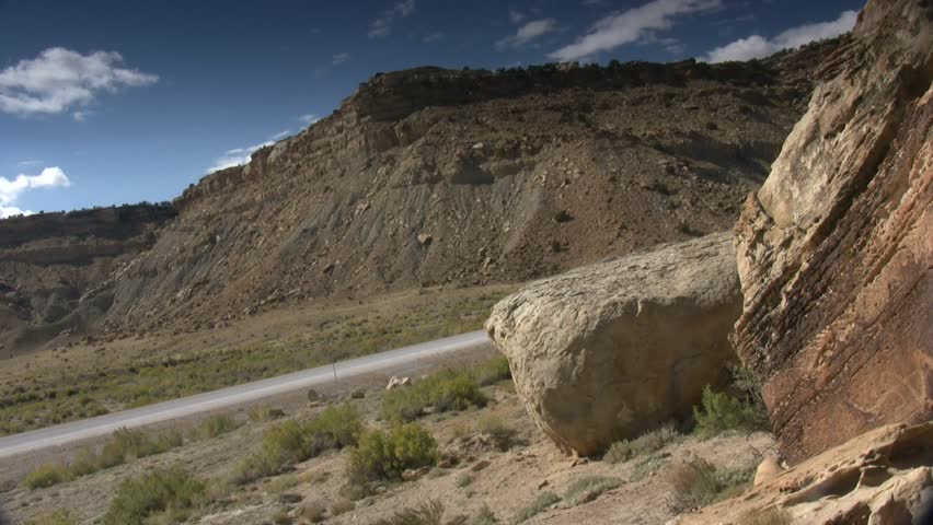 Wide shot; Pan right to snake petroglyph on large boulder, neutral grad sky.