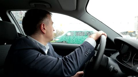 Respectable, responsible man driving car. Raining day. Dangerous road. The man in a suit. the man holds the steering wheel. Close up