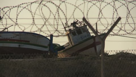 Ship graveyard in Lampedusa. Abandoned ships of immigrants from Africa behind fence in the refugees camp 3