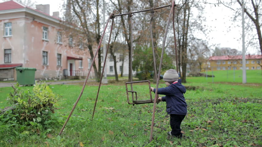 The little boy is swinging an old swing. #3198367