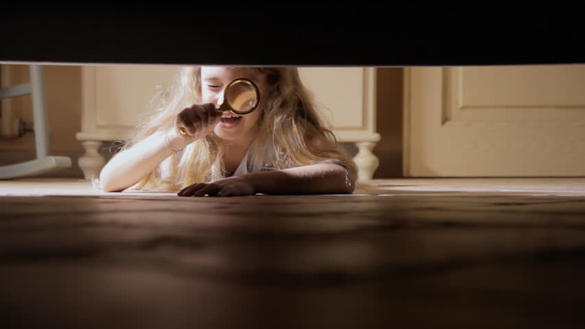 A little girl finding something under the bed with a magnifying lens glass.
