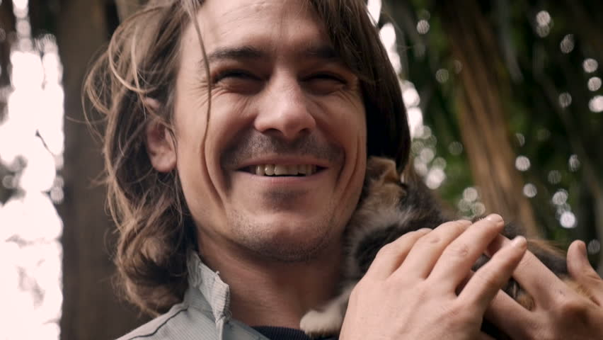 Happy smiling and laughing attractive man holding a tiny kitten near his face in slow motion