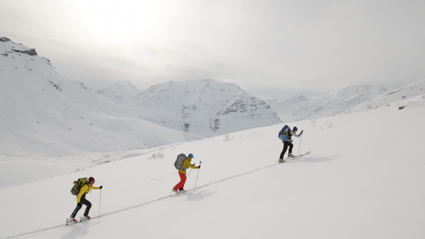 A group of backpack laden hikers ski up a dangerous snow and ice covered mountain face in Alaska during the day while the wind blows clouds around | Shutterstock HD Video #3201637